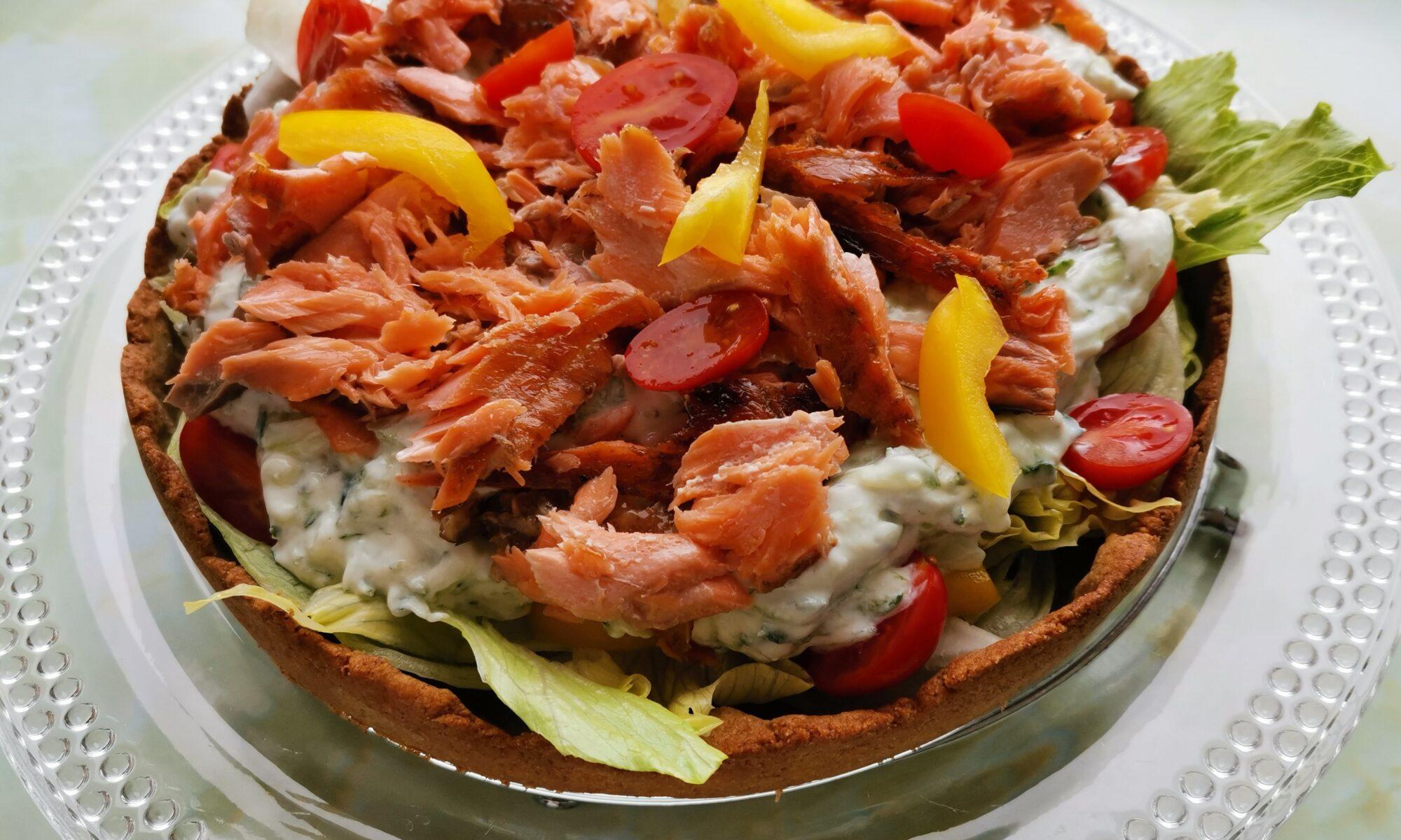 Salaattipiirakka lohella ja tsatsikilla, lasilautasen päällä